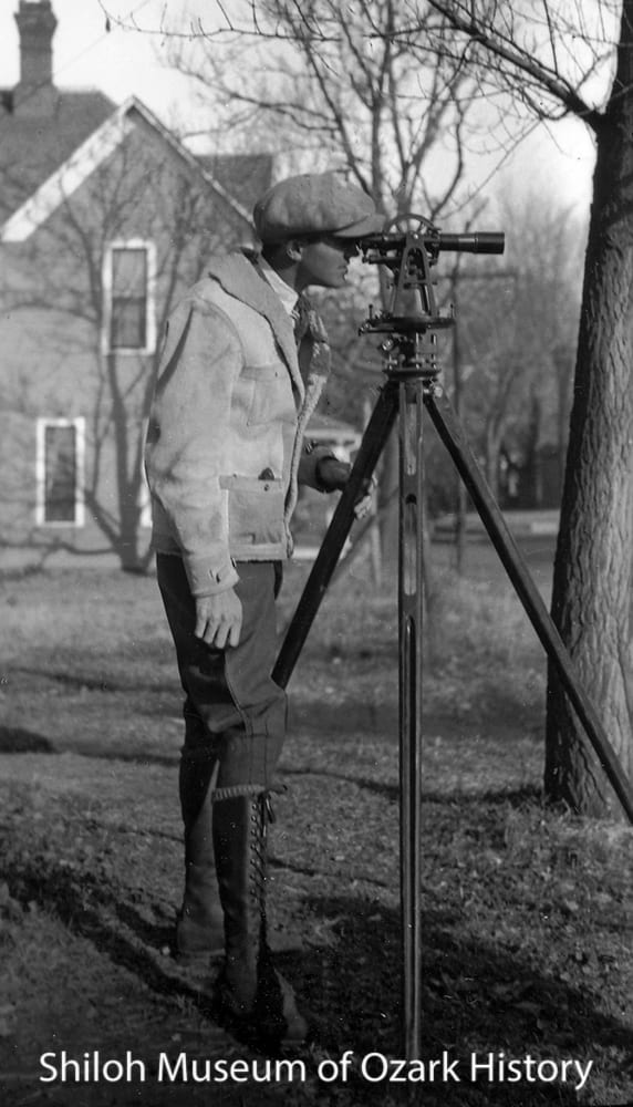 Carl Smith with his surveying equipment at his mother's home on Locust Street, Fayetteville, about 1925.