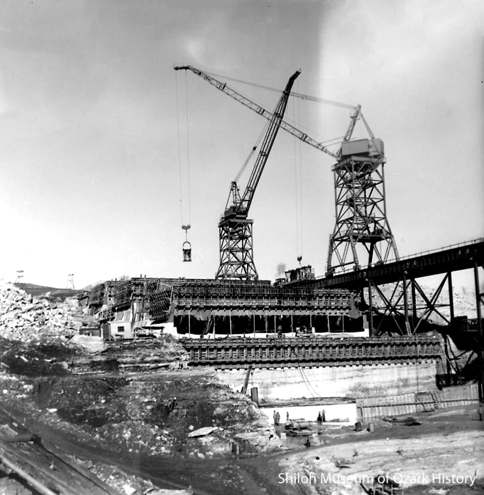 Whirley cranes moving buckets of concrete to a monolith, December 1961.