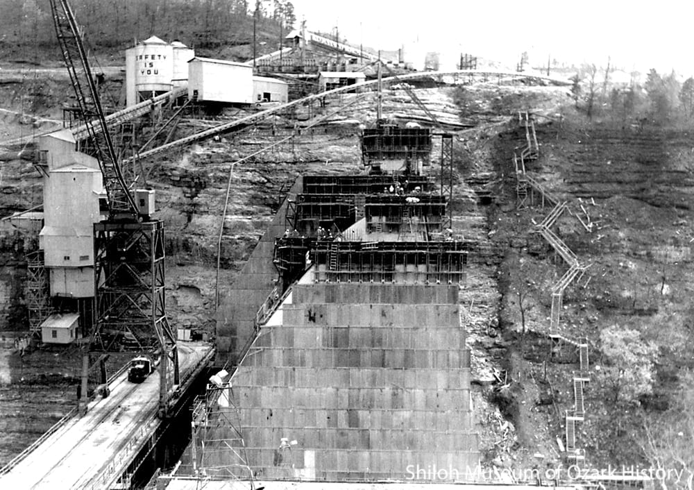 Slip forms used to construct the narrow, arched walls of the spillway, April 1963.  Below the gantry the dinkey locomotive hauls a flatcar of concrete.