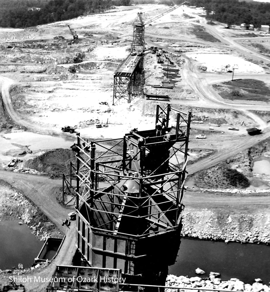 The concrete mixing plant (front) and the trestle for the whirley cranes (back) under construction, August 1961. The White River flows below the concrete plant.