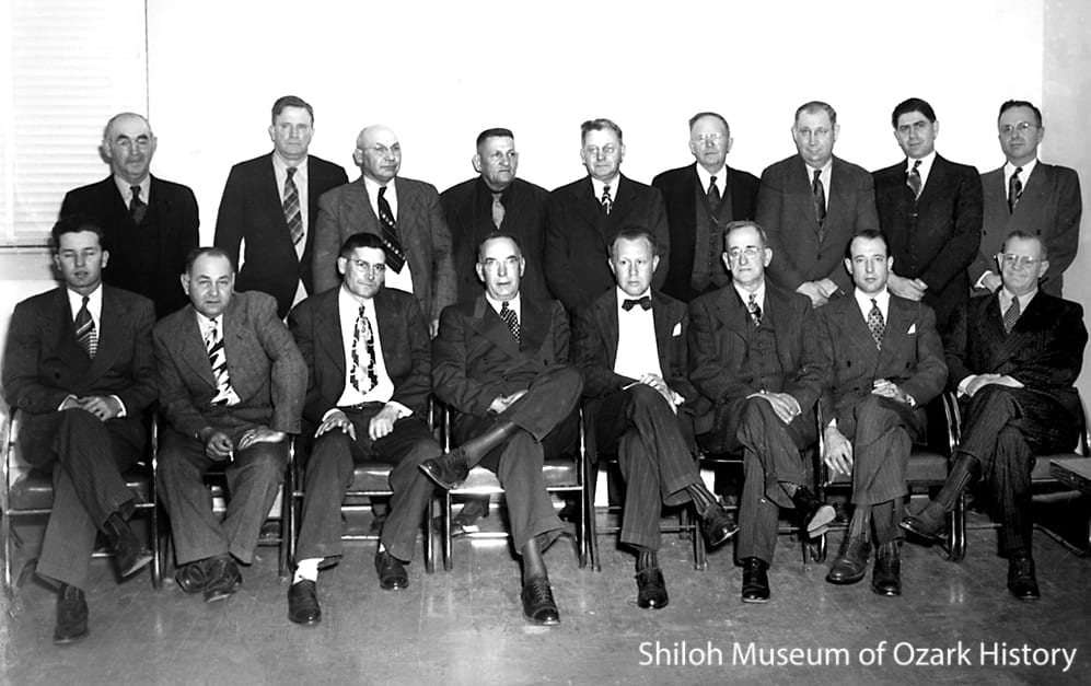 Members of the Beaver Dam Association, circa 1950.  Front row, from left: Willis Shaw (Elm Springs), Claud Morsani (Tontitown), vice-president Joe Robinson (Springdale), president Earl Harris (Rogers), secretary-treasurer Courtney Crouch (Springdale), Mace Howell (Springdale), Paul Young (Fayetteville), unidentified.  Back row, from left:  Elbert Graham (Lowell), State Senator Russell Elrod (Siloam Springs), J.J. Neil (Springdale), Albert Price (Eureka Springs), unidentified, unidentified, Shelby Ford (Springdale), Carl Shores (Cave Springs), unidentified.