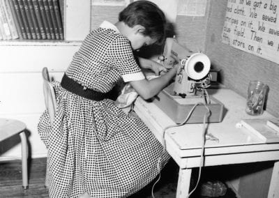 Child sewing a piece of clothing, Springdale, August 1960.