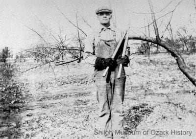 Benjamin F. Smith holding loppers in his orchard near the White River, east of Springdale, 1910s.