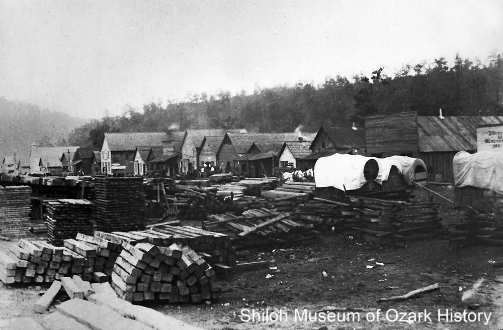 Stacks of railroad ties, split-rail fencing, and boards await shipment in downtown Pettigrew (Madison County, Arkansas), 1900s–1910s.