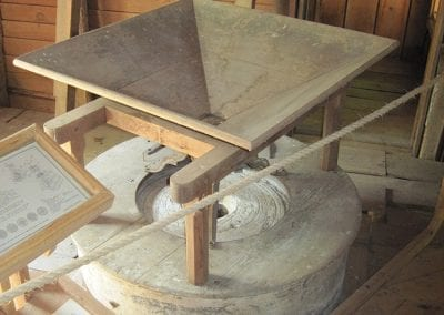 Millstone assembly, first floor. These millstones were used exclusively to grind corn once roller mill equipment was added to process wheat. As grain was put into the wooden hopper (on top), it fell through the eye of the runner stone and onto the flat surface of the bed stone, where it was ground. The top part of the runner stone is made of plaster.