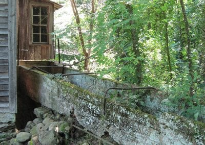 Office addition and flume at the back of the mill. The rotting wood flume was replaced with concrete around 1901.