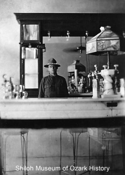 Private Steve Georgenis behind the soda fountain of his candy kitchen, Fayetteville, mid-late 1910s.