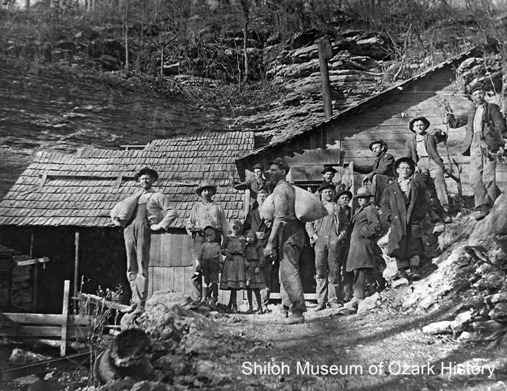 Men with sacks of corn at the Bat House Cave distillery, Wells Creek, near Hasty, Newton County, Arkansas,1900s-1910s.