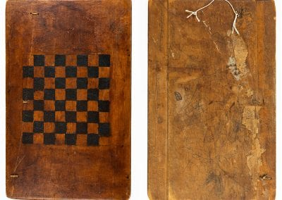 Checkerboard possibly made from a cabinet-door panel, with rawhide strips used to mend a break in the wood, possibly 1900s. Used by the Vaughan family of Hindsville, Arkansas..