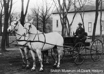 Noted horseman Carl Ownbey Sr. with his matched pair of horses, Spring Street, Springdale, Arkansas, early 1900s.