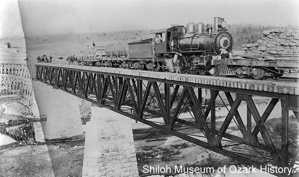 Engine #3 pushing a lumber car during the construction of the St. Louis & North Arkansas Railroad bridge, Kings River, Grandview (Carroll County, Arkansas), 1901.