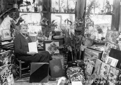 "Maggie Glover Morgan with her scrapbooks, other mementoes, and her parrot, ""Pollie,"" Springdale, Arkansas, 1930s."