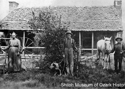 The Joseph M. Smith family with their spinning wheel, hunting dog and rifle, and horse, southeast Washington County, Arkansas, early 1900s.