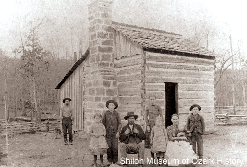 The Wesley Graham family by their single pen log cabin, Monitor Community near Springdale (Washington County), circa 1893.