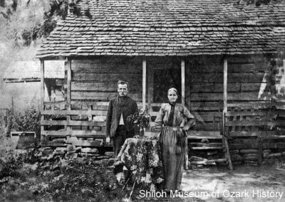 Robert and Parmilla Sullins with their draped table and vase of flowers, Japton, Arkansas, early 1900s.
