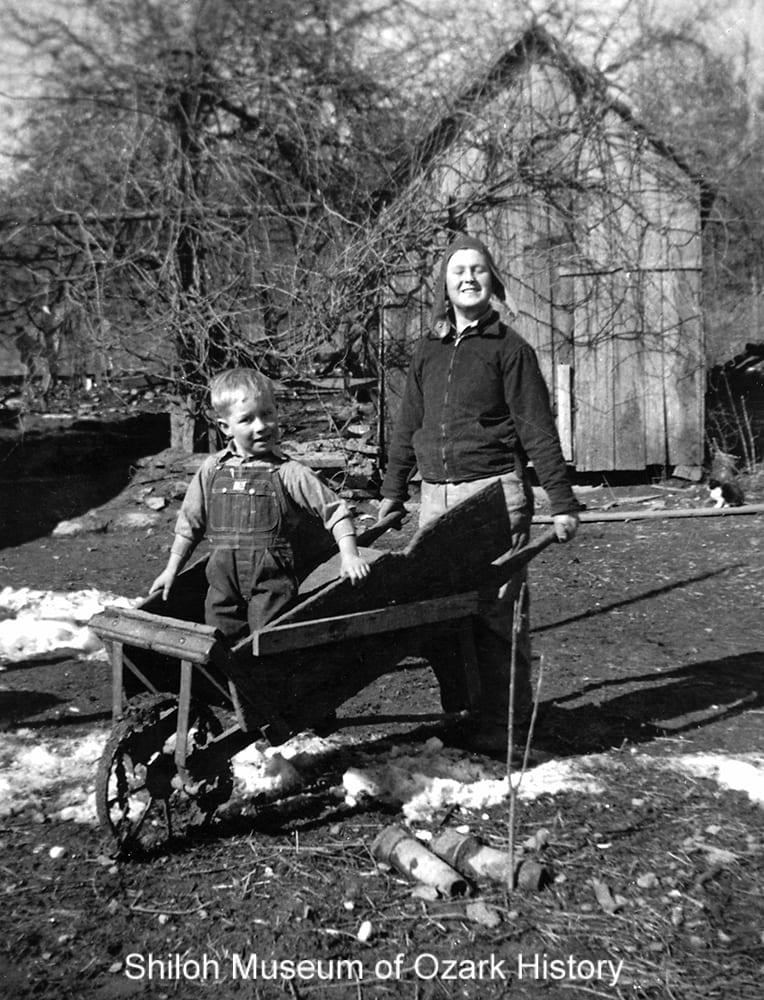 Clyde Barker pushing Wayne Martin in a wheelbarrow, Pettigrew, Arkansas, circa 1940.