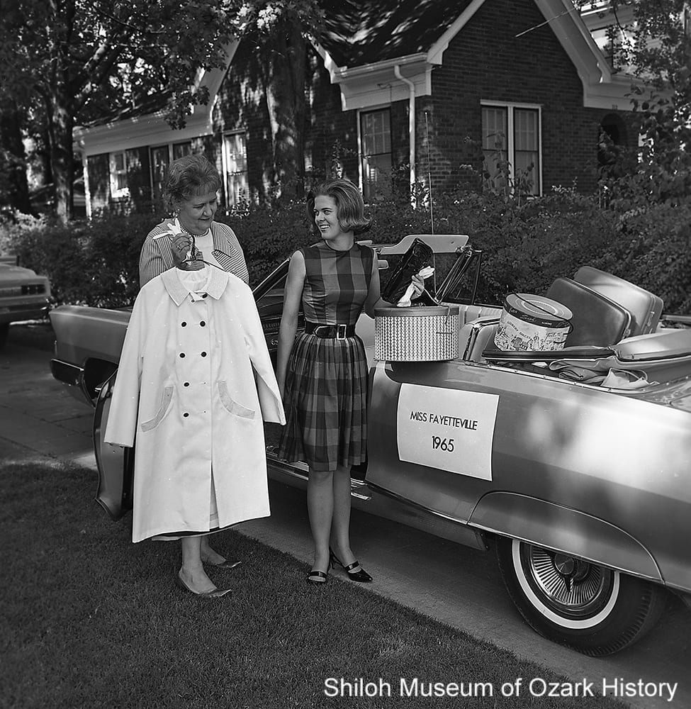 "Elizabeth ""Betsy"" Bridenthall (right), Miss Fayetteville 1965, receives gifts of clothing, luggage, and the keys to a new car, Fayetteville, Arkansas, April 1965."