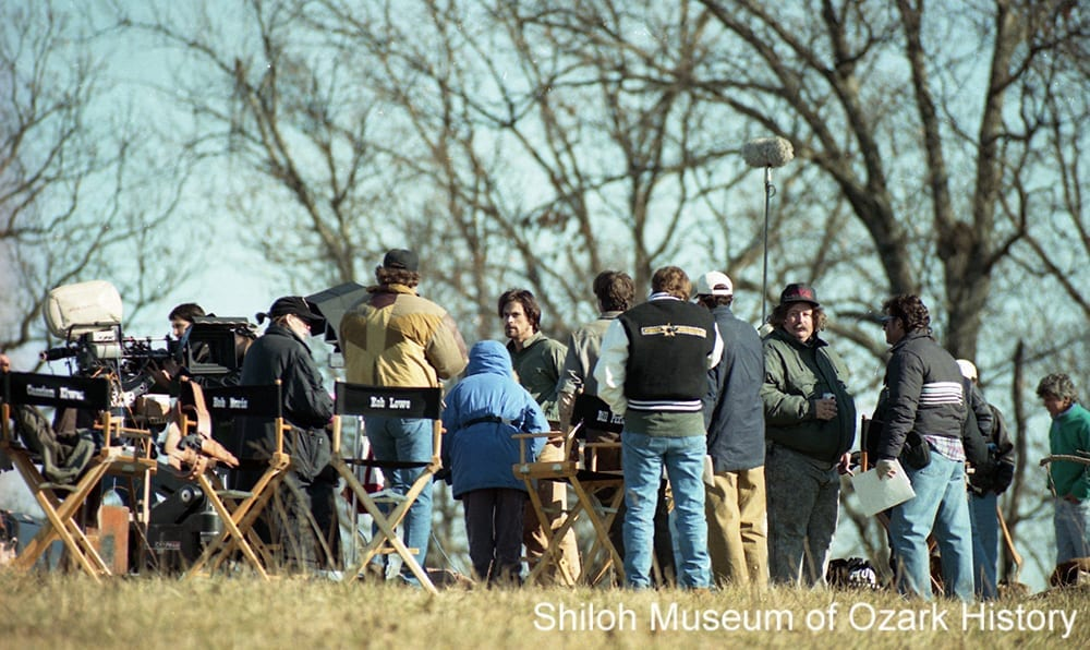 Surrounded by crew members, star Rob Lowe (center, with beard) prepares to shoot a stump-pulling scene for Frank and Jesse, Fayetteville, Arkansas, 1993