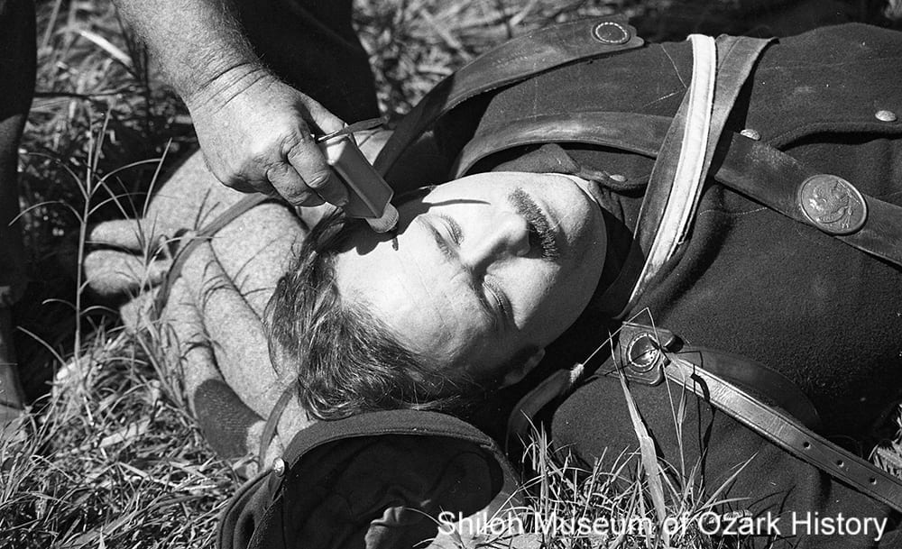 "A re-enactor receives a ""head wound"" from a makeup artist during filming of The Blue and the Gray, Prairie Grove Battlefield State Park, October 2, 1981."