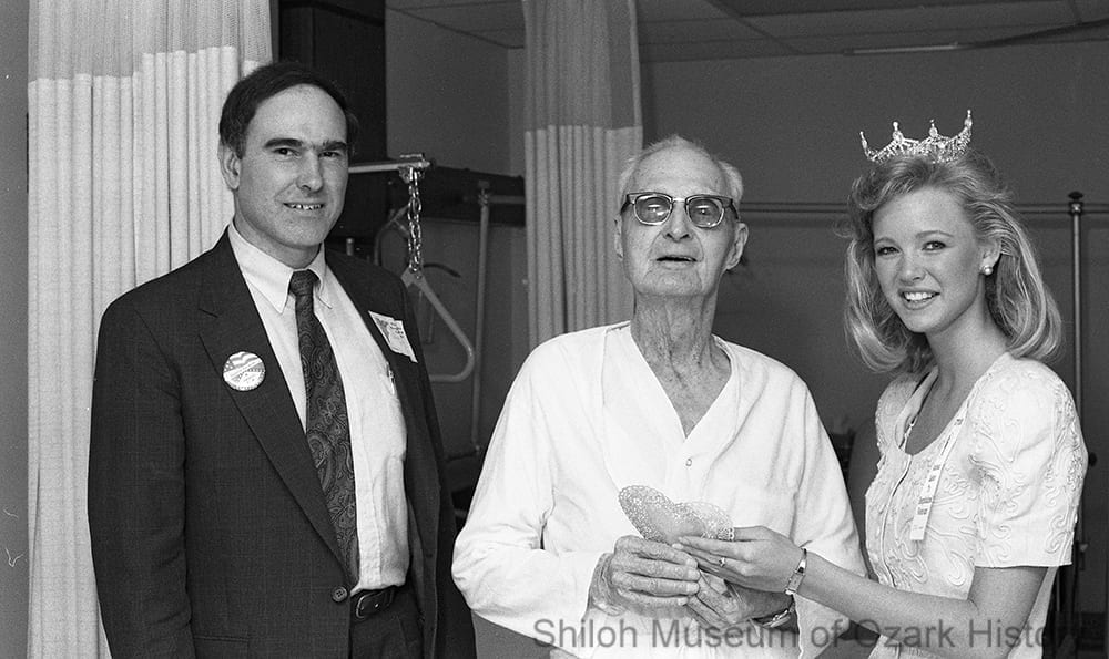 "Shannon Boy, Miss Northwest Arkansas 1990, hands a Valentine to Milton Boyd, as part of a ""National Salute to Hospitalized Veterans"" celebration, Veterans Administration Medical Center, Fayetteville, Arkansas, February 14, 1991."