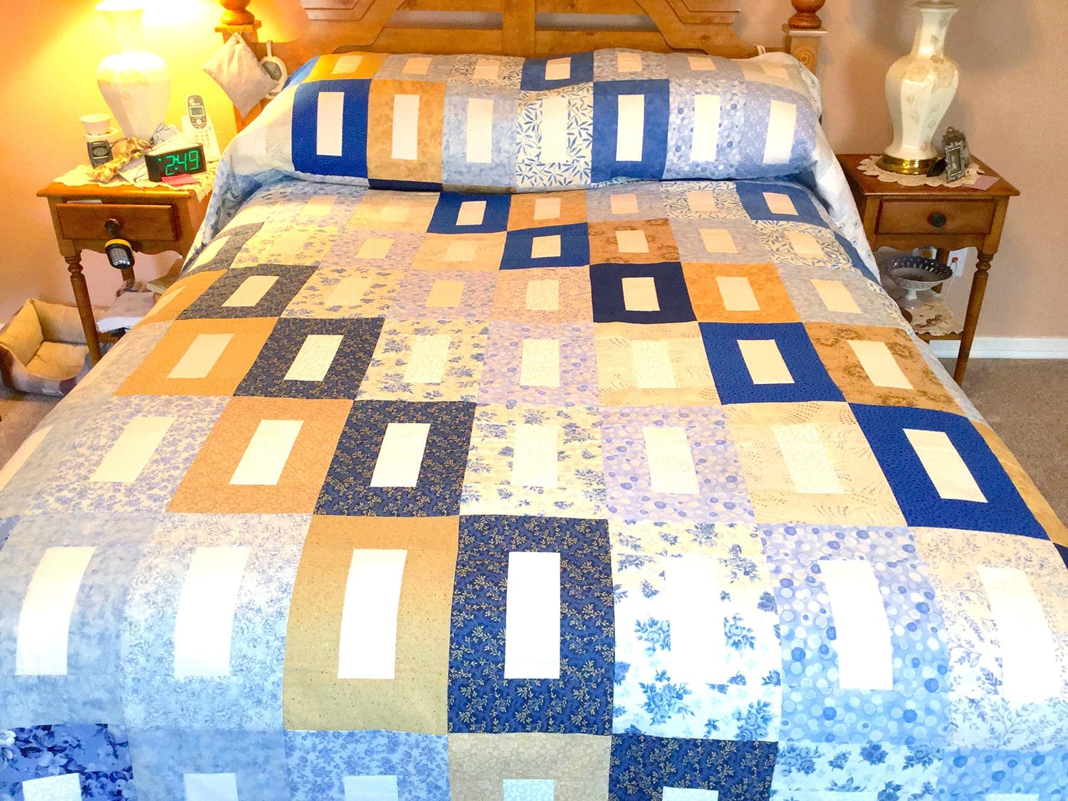 Quilt on bed with various blue and gold patterned rectangles with white centers.