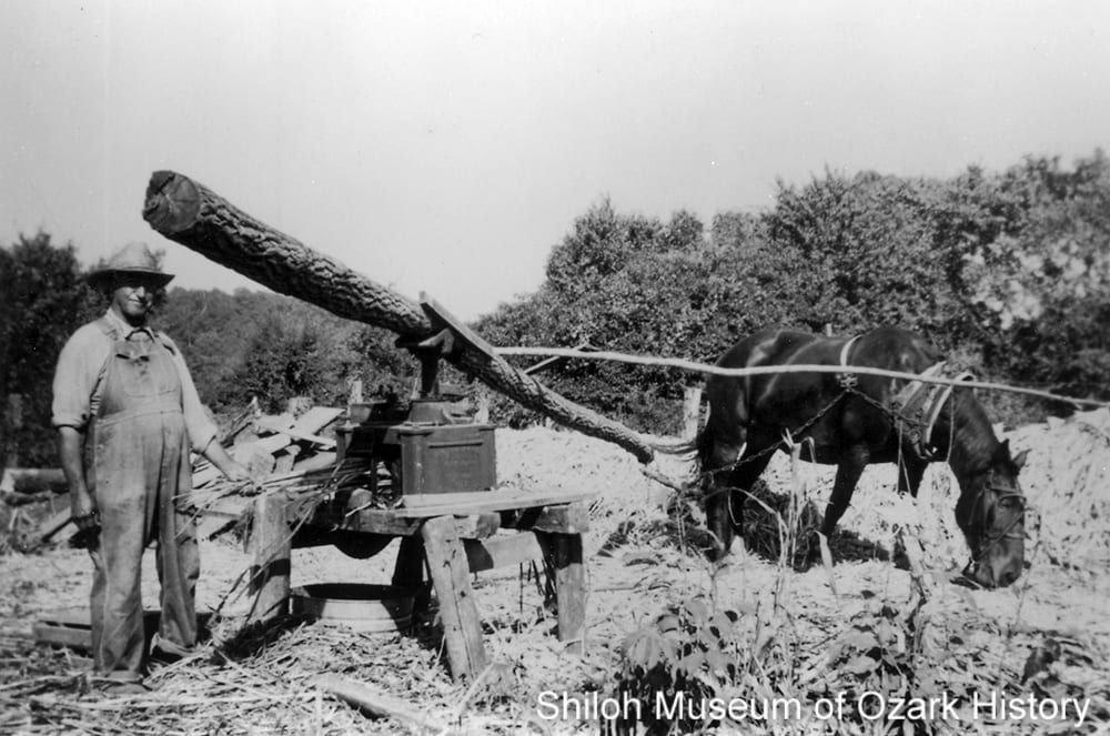 Henry Tarleton Lane feeding sorghum stalks into a mill, Kingston area (Madison County, Arkansas), circa 1953
