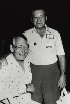 Black and white photo of two men, one is standing and one is seated. They are smiling.
